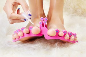 body part shot of healthy woman's feet in pedicure toe separators. hand is putting polish on toenail